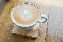 Café chaud de latte dans la tasse en verre de tasse sur la table Photo libre de droits