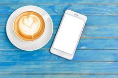Café chaud de latte de vue supérieure dans la tasse et le smartphone blancs avec le blanc Photos stock