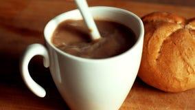 Café chaud et lait affluant dans la tasse blanche au-dessus de la table en bois Café se renversant de main de femme avec du lait  clips vidéos