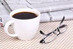 Café chaud frais sur le journal Photos stock