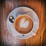 Café chaud italien de cappuccino avec la mousse en forme de coeur sur la table en bois Images libres de droits