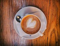Café chaud italien de cappuccino avec la mousse en forme de coeur sur la table en bois Photographie stock