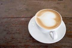 Café chaud sur la table avec la forme de coeur sur la tasse blanche Copiez l'espace Photos stock