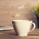 Café chaud sur le bureau en bois de travail Image libre de droits