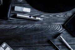 Café, cigarrillo electrónico, backg de madera oscuro de los accesorios para hombre Imagenes de archivo
