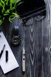 Café, cigarrillo electrónico, opinión superior del fondo de madera oscuro para hombre de los accesorios Imágenes de archivo libres de regalías