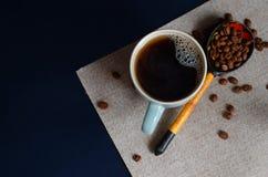 Café colombiano fuerte en una taza verde clara y un arabica entero de los granos de café Visión superior Foto de archivo libre de regalías