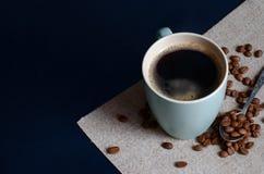 Café colombiano fuerte en una taza verde clara y un arabica entero de los granos de café Visión superior foto de archivo
