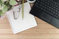 Café com caderno, flor, lápis, vidros do olho no backgroun de madeira Fotografia de Stock Royalty Free