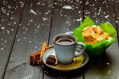 Café com canela e bolo em uma tabela de madeira preta imagens de stock royalty free