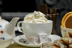 Café com creme e bolos na tabela imagem de stock