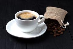Café com espuma em um copo branco e um saco das grões em um fundo preto fotos de stock