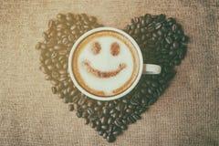 Café com teste padrão do sorriso da arte do leite da espuma na forma do coração Imagem de Stock Royalty Free