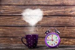 Café com vapor e despertador da forma do coração Fotos de Stock Royalty Free