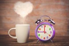 Café com vapor e despertador da forma do coração Imagem de Stock Royalty Free