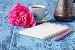 Café con el cuaderno, y la flor de la peonía Imagen de archivo libre de regalías