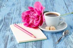 Café con el cuaderno, y la flor de la peonía Fotografía de archivo