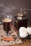 Café con humo en la taza y el canela de cristal con el céfiro Foto de archivo libre de regalías