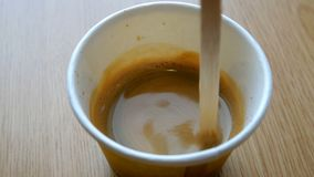 Café con la espuma mezclada con un palillo de madera, en una taza de papel disponible almacen de metraje de vídeo
