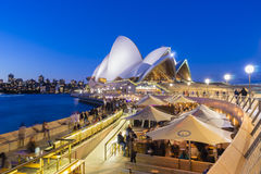 Café con la gente y Sydney Opera House en el crepúsculo Fotos de archivo libres de regalías