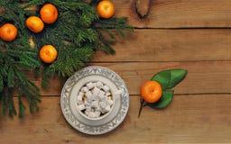 Café con la melcocha, las ramas spruce y los mandarines en un fondo de madera La Navidad y Año Nuevo Foto de archivo
