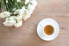 Café con las flores en la tabla de madera Imagenes de archivo