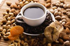 Café con las tuercas, el higo y los albaricoques secados Foto de archivo libre de regalías