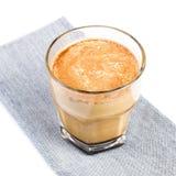 Café con leche en una taza de cristal en el mantel de lino aislado encendido Imagen de archivo