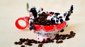 Café con leche: Juegue la vaca que se sienta en la taza roja del cofee con como en el baño Imágenes de archivo libres de regalías