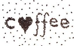 Café con un corazón escrito en granos de café Fotos de archivo libres de regalías