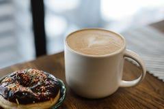 Café con un corazón y una leche exhaustos en una tabla de madera fotografía de archivo libre de regalías