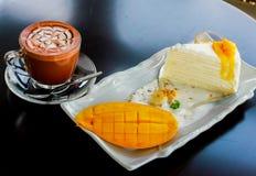 Café con un pedazo de pastel de queso del mango en la tabla de madera Foto de archivo