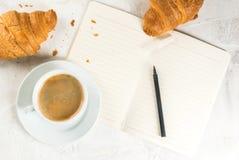 Café, croissants et bloc-notes photographie stock libre de droits