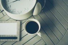 Café, cuaderno y despertador en la tabla de madera Fotografía de archivo