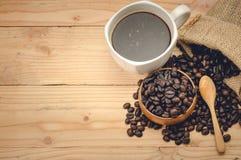 café d'americano et grains de café sur la table en bois Images libres de droits