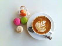 Café d'art de Latte avec des macarons si délicieux sur le blanc images stock