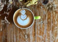 Café d'art de latte de coeur dans la tasse blanche sur la table en bois de vintage et le premier plan sec de fleur Photographie stock libre de droits