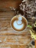Café d'art de latte de coeur dans la tasse blanche sur la table en bois de vintage et le premier plan sec de fleur Photo libre de droits