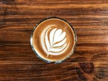 Café d'art de latte de coeur en verre sur le vintage en bois Photographie stock libre de droits