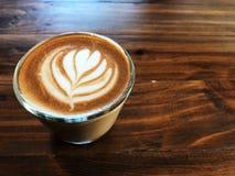 Café d'art de latte de coeur en verre sur le vintage en bois Image libre de droits