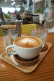 Café d'art de latte de forme de coeur sur la table de bois de construction dans le café Image stock