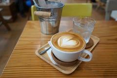 Café d'art de latte de forme de coeur sur la table de bois de construction dans le café Images stock