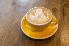 Café d'art de latte de Rosetta et tasse jaune sur la table en bois Image stock