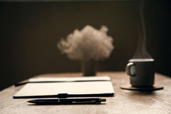Café d'expresso, album avec le stylo Table d'auteur Cuvettes de café et grains de café frais autour Détente Fin vers le haut Photo libre de droits