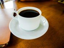 Café d'expresso dans une tasse blanche placée sur une table en bois images stock