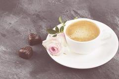 Café d'expresso en tasse blanche, rose rose et chocolats sur a Photographie stock
