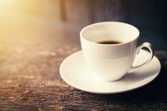 Café d'expresso ou café noir d'Americano dans la tasse blanche sur la table en bois Photos stock