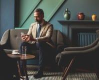 Café d'homme d'affaires supérieur et téléphone portable potables d'utilisation dans le lob Photographie stock