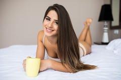 Café da bebida da menina em sua manhã do am da cama fotografia de stock royalty free