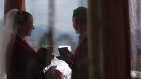 Café da bebida do noivo e da noiva ou chá fora dos copos em um balcão da casa de campo de madeira do chalé do log na vila e do be filme